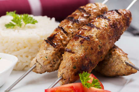 rice plate: Barbecued kofta - kebeb with rice and vegetables on a plate. Selective focus