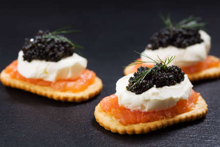 Zwarte kaviaar geserveerd op crackers met zalm en roomkaas.