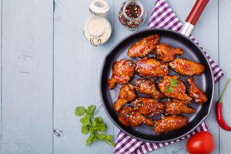 Alitas de pollo cocidas al horno en salsa de miel rociados con semillas de sésamo.