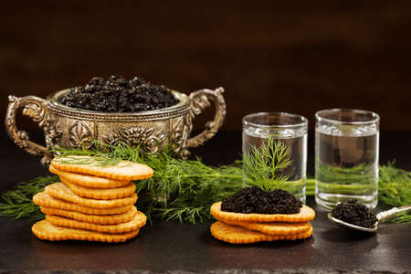 additives: Black caviar served on crackers with vodka and additives Stock Photo