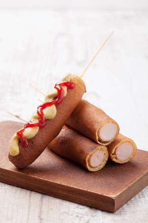 perro comiendo: perro de maíz. Salchicha cocida en masa de maíz servido con salsa de tomate y mostaza en una bandeja de papel. Foto de archivo
