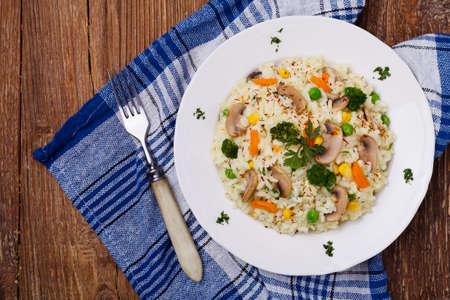 comida italiana: Risotto clásico con setas y verduras servido en un plato blanco.