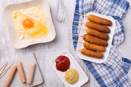 fast meal: Corn dog. Sausage baked in corn dough served with ketchup and mustard on a paper tray.