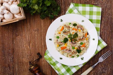 Classic Risotto met paddestoelen en groenten geserveerd op een witte plaat. Stockfoto - 52537269