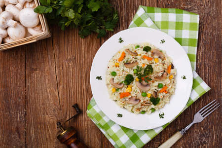 Classic Risotto with mushrooms and vegetables served on a white plate.