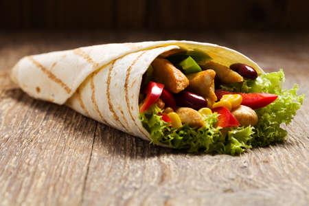 comidas rapidas: Burritos envuelve con pollo, frijoles y verduras en la tabla de madera