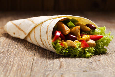 fast meal: Burritos wraps with chicken, beans and vegetables on wood board Stock Photo