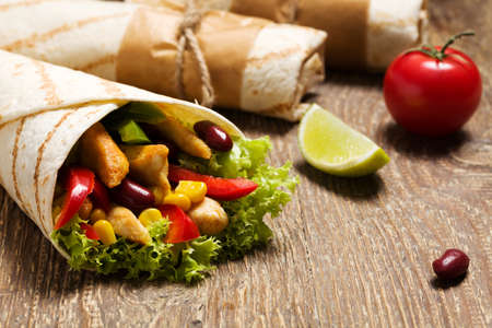 delicious food: Burritos wraps with chicken, beans and vegetables on wood board Stock Photo