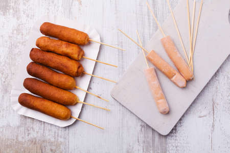 dog white background: Corn dog. Sausage baked in corn dough served with ketchup and mustard on a paper tray.