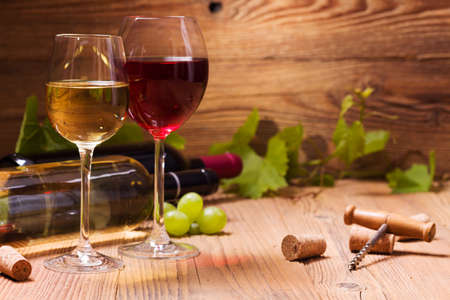 Glasses of red and white wine, served with grapes on a wooden background