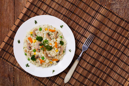 mushroom: Classic Risotto with mushrooms and vegetables served on a white plate.