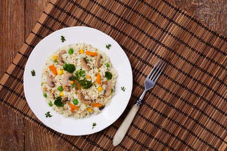 hongo: Risotto clásico con setas y verduras servido en un plato blanco.