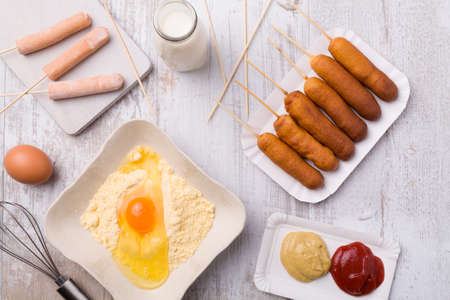 snack food: Corn dog. Sausage baked in corn dough served with ketchup and mustard on a paper tray.