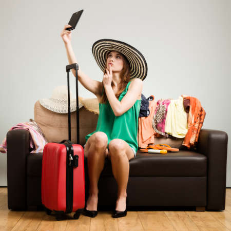 easy going: Young woman in a hat with a traveling bag does selfie on the sofa before going on holiday. Gray background, easy to remove.