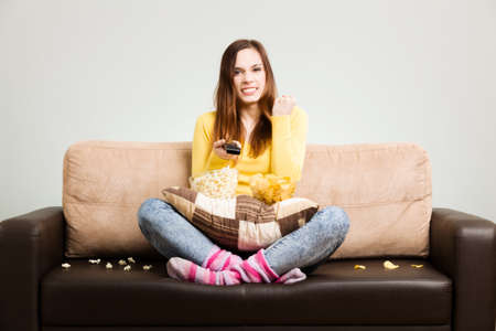 munching: Young woman spends his free time watching TV on the couch at home, munching chips and popcorn. Gray background, easy to remove.