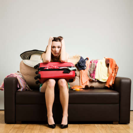 pushes: Young woman packing a travel bag on the plane before going on holiday. Gray background, easy to remove. Stock Photo
