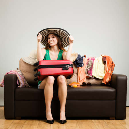 easy going: Young woman packing a travel bag on the plane before going on holiday. Gray background, easy to remove. Stock Photo