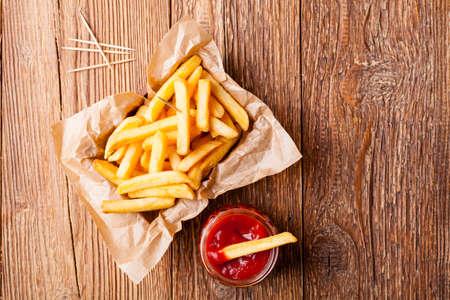 Vers gebakken frieten met ketchup op houten achtergrond Stockfoto