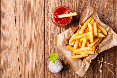 Fresh fried french fries with ketchup on wooden background Zdjęcie Seryjne