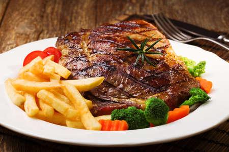carne de res: filete de carne a la parrilla servido con papas fritas y verduras en un plato blanco.
