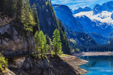 alp: The snow-covered peaks in the Alps with a beautiful green mountain slopes. In the bottom of the lake. Stock Photo