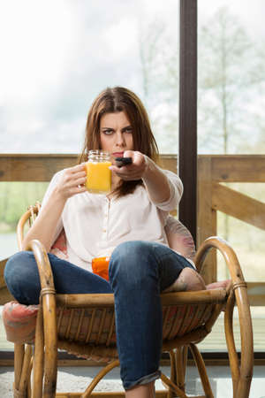 munching: Young woman spends his free time watching TV on the rocking chair at home, munching chips and popcorn, drink orange juice from the jar. Stock Photo