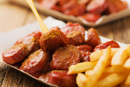 Traditional German currywurst, served with chips on disposable paper tray. Wooden table as  background. Imagens - 57915647