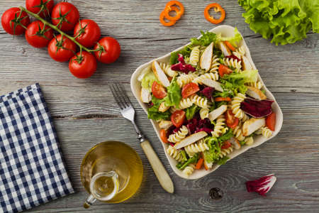 Delicious pasta salad with green salad, tomatoes and roasted chicken. Stock Photo