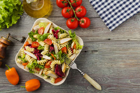 Delicious pasta salad with green salad, tomatoes and roasted chicken. Banco de Imagens
