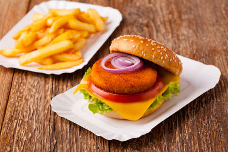 breading: Delicious fish burger served with fresh french fries, served on a paper try.