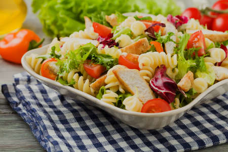 rotini: Delicious pasta salad with green lettuce, tomatoes and roasted chicken. Stock Photo