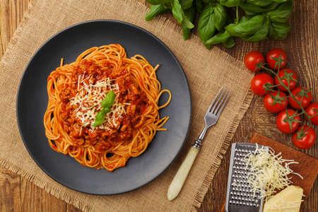 Heerlijke spaghetti die op een zwarte plaat wordt gediend Stockfoto
