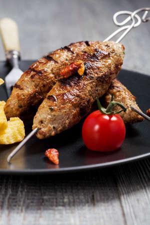 Kofta a la parrilla - kebeb con papas fritas y verduras en un plato. Enfoque selectivo