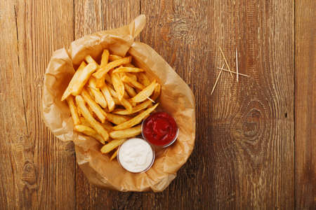 Serving Belgian fries served on paper in the basket, with one or two dips. On a wooden table.