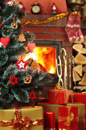 Christmas presents under the Christmas tree on the background of a roaring fireplace.
