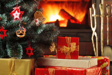 Regalos de Navidad bajo el árbol de Navidad en el fondo de una chimenea.
