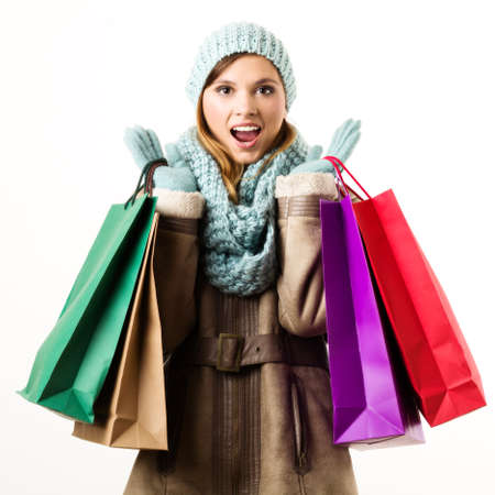Young woman on Christmas sales in winter clothes with colorful bags. White background.