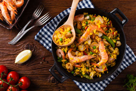 Traditional Spanish paella with seafood and chicken. Prepared in wook. Top view. Standard-Bild