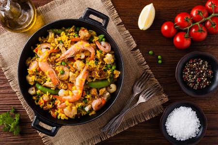 Traditionele Spaanse paella met zeevruchten en kip. Bereid in wook. Bovenaanzicht.