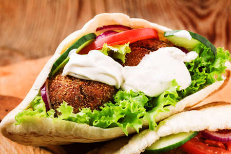falafel: Falafel and fresh vegetables in pita bread on wooden table
