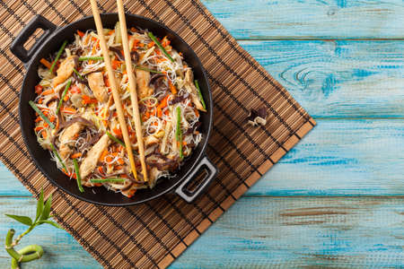 Rice noodles with chicken, mushrooms mun and vegetables, prepared in wok. Top view. Foto de archivo