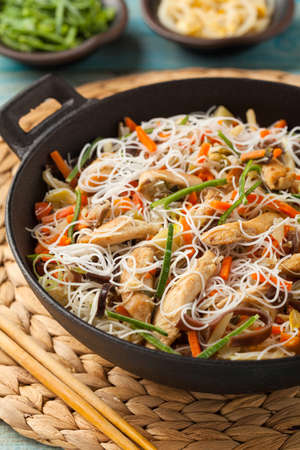 Rice noodles with chicken, mushrooms mun and vegetables, prepared in wok.
