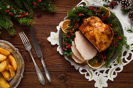 Prosciutto al forno di Natale, servito sul vecchio piatto. Ramoscelli di abete tutt'intorno. Vista dall'alto. Archivio Fotografico - 63696422