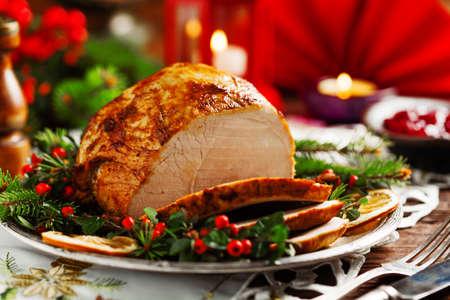 Vánoční pečená šunka, podávaná na staré desce. Smrkové větvičky všude kolem. Čelní pohled.