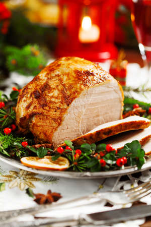 Christmas baked ham, served on the old plate. Spruce twigs all around. Front view. Reklamní fotografie - 64613131