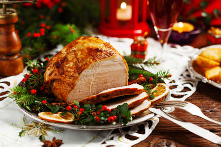 Christmas baked ham, served on the old plate. Spruce twigs all around. Front view. 版權商用圖片 - 64613132