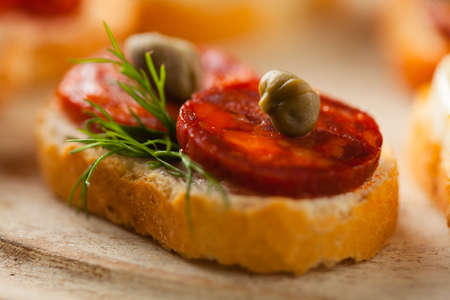 caper: Crostini with different toppings on wooden background. Delicious appetizers. Front view.