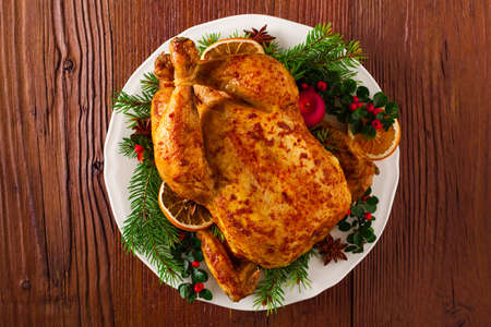 whole chicken: Roasted whole chicken with Christmas decoration. Wooden background. Top view.
