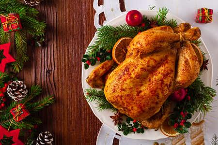크리스마스 장식과 함께 전체 치킨을 구운. 목조 배경입니다. 평면도.