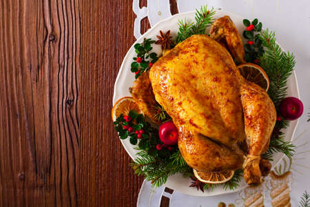 Stil: Roasted whole chicken with Christmas decoration. Wooden background. Top view.
